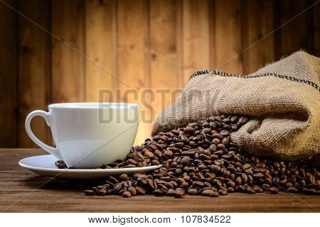 still life with coffee beans , cup and small sack  on the wooden background