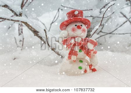 Toy of the snowman in snow