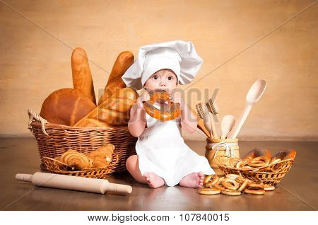Little Cook. Small Kid In A Chef's Hat With Wicker Baskets Of Pastries, Rolls, Bread And Bagels