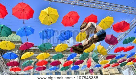 Man In The Air On Street Decorated With Cman In The Air On Street Decorated With Colored Umbrellas