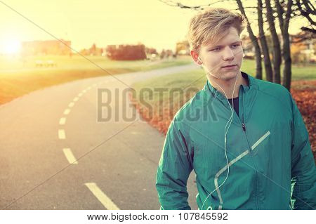 Young Man Runner With Headphones In Autumn Park