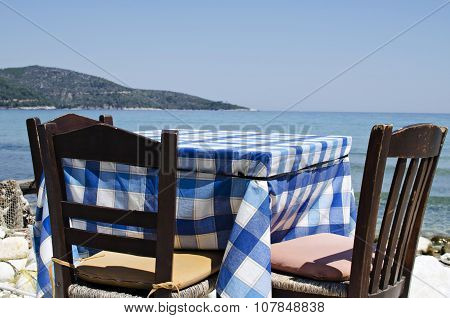 Table and chairs in front of the sea