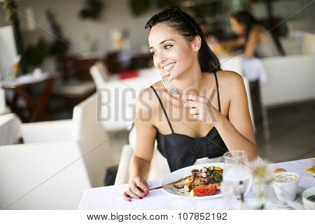Young Woman Eating In The Restaurant