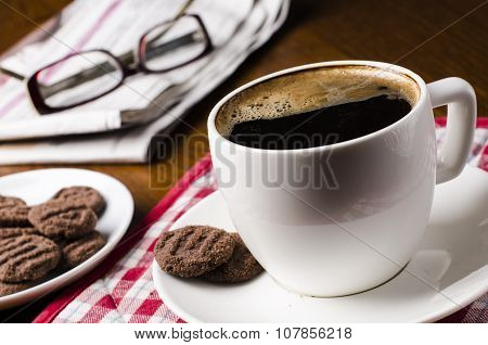 Cup of coffee on a red tablecloth. on a left side are cookies and news with glasses. natural