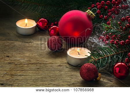 Red Baubles, Candles And Fir Branches As Christmas Decoration On Rustic Wood