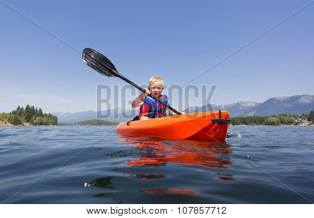 Young Boy paddling a kayak on a beautiful mountain lake. Low angle view of the nature's beauty