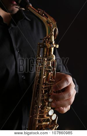 Musician in black shirt with sax on dark background, close up