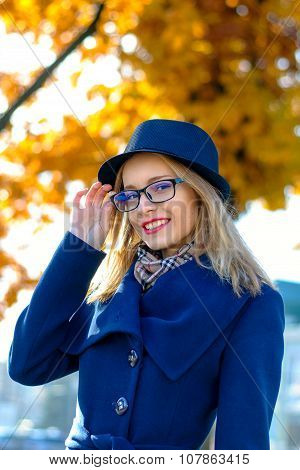 Blond Woman In A Blue Hat Straightens Glasses