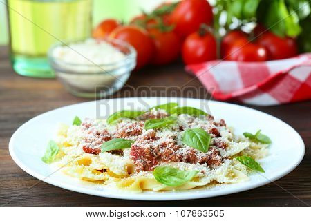 Pasta bolognese in white plate on wooden table, closeup