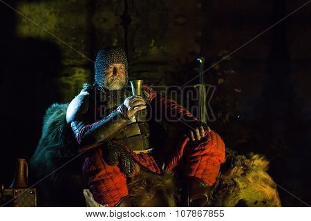 Old Medieval King In Armor With Dish Is Sitting On Furs Near The Camp Fire And Drinking Wine