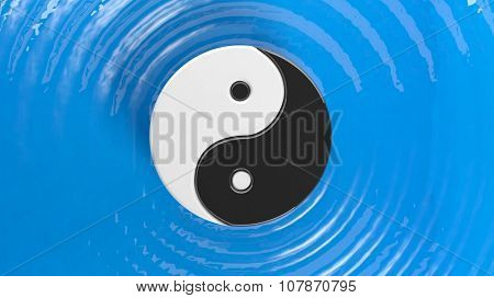 Yin and Yang symbol on blue water with ripples