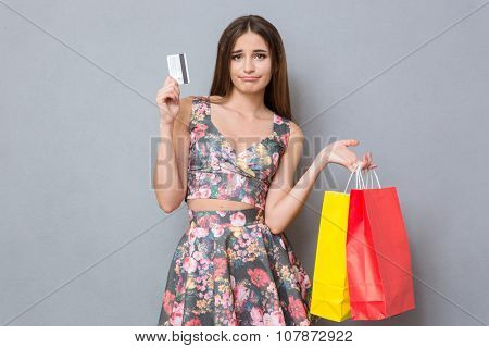 Sad disappointed pretty girl with credit card and colourful bags