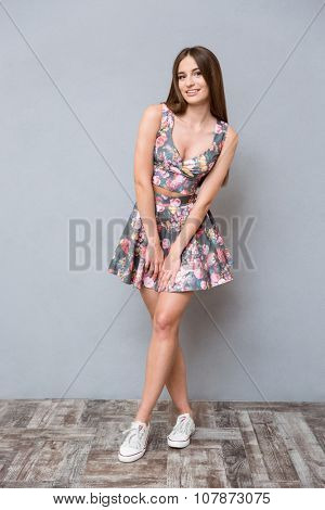 Lovely sweet cute pretty happy smiling girl with long hair in floral summer suit posing on gray backgroung