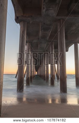 Under the Huntington Beach, California pier at sunset