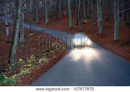 Car With Headlights On Country Road