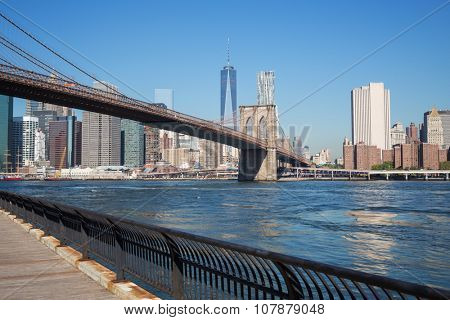 Cityscape of Brooklyn Bridge across East River at autumn sunny day.