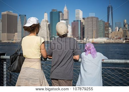 Back view of family of three are standing on the quay at autumn day.