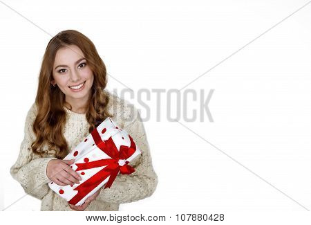 Christmas woman holding present excited.wearing santa hat looking to side showing gift isolated on w