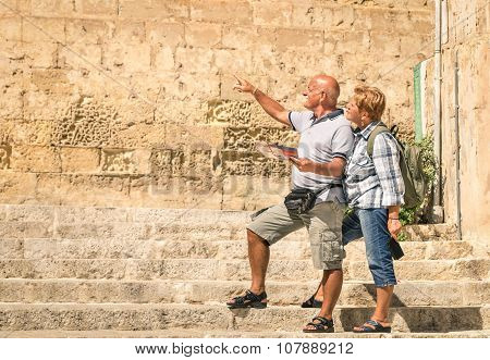 Happy Senior Couple Exploring Old Town Of La Valletta With City Map - Concept Of Active Elderly