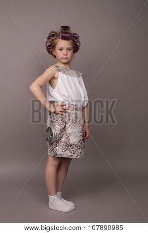 portrait of the little girl in hair curlers