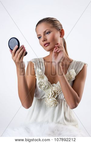 Young Woman Looking In The Mirror