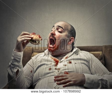 Voracious man eating a hamburger