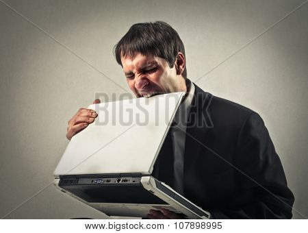 Angry employee biting his laptop