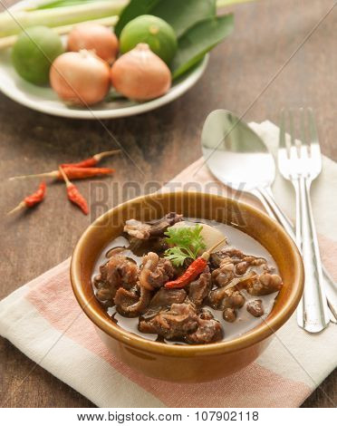 Thai beef curry in brown bowl on wood table.
