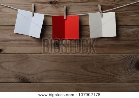 Three Opened Greetings Cards Pegged On String Against Wood Planking