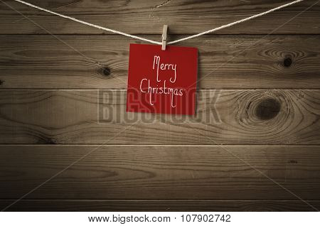 Merry Christmas Message On Red Note Paper Pegged To String Against Wood Planks