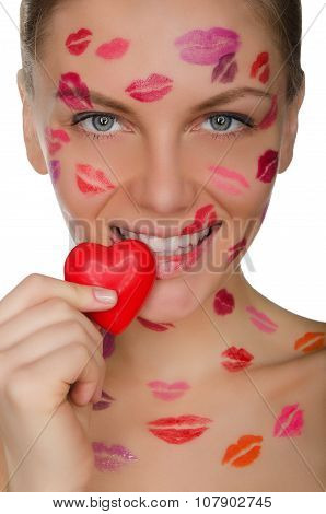 Young Woman With Kisses On Face Holding Heart In Mouth