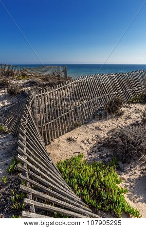 Ancient Wooden Fence On The Background Of The Sea, The Beach. Portugal Algarve.