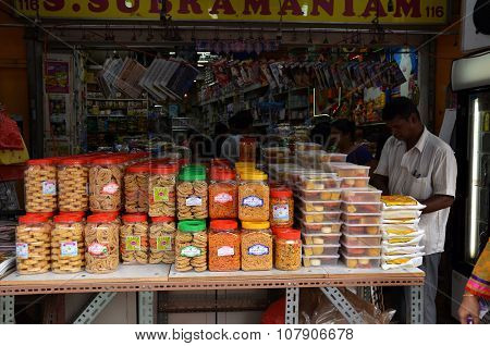Young Men Selling Local Snacks At Stall On A Pavement In Little India, Singapore.
