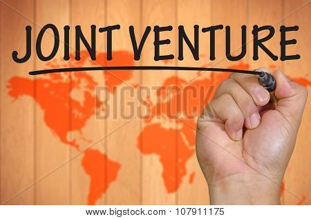 Hand Writing Joint Venture Over Blur World Background