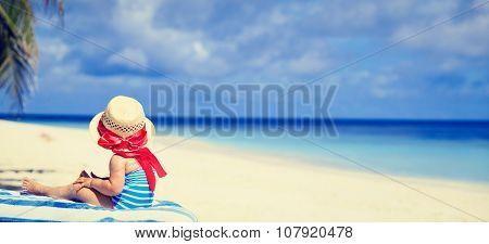 little girl in big hat on summer beach