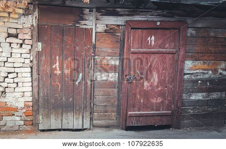 Two old wooden doors and compound wall of a shed made of planks and bricks