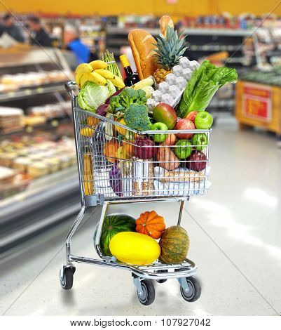 Grocery shopping cart with vegetables and fruits in a supermarket.