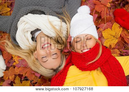 Two friends laying in leafs with closed eyes