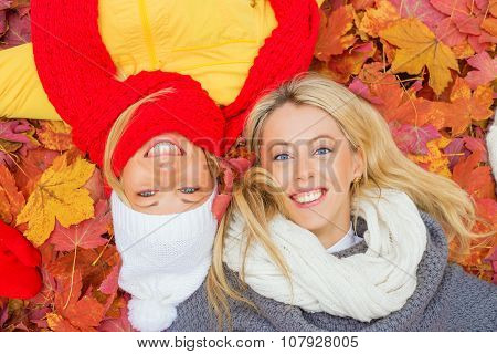 Two happy girlfriends laying in leafs and smiling