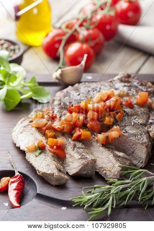 Beef steak well done with tomato and pepper salsa