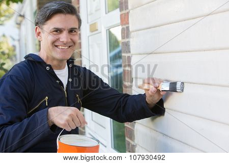 Man Holding Brush And Tin Painting Outside Of House