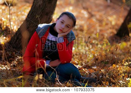 The Sad Girl Sits On An Autumn Grass.