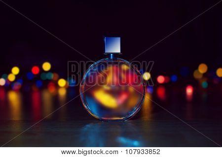 Perfume Bottle On Christmas Lights Background.