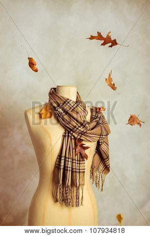 Tailors dummy wearing scarf with falling autumn leaves
