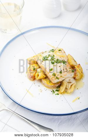 Roasted cod, codfish with baked potatoes and artichokes