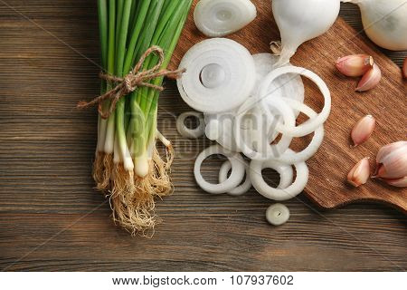 Onions circles, fresh green onion with garlic on board against wooden background