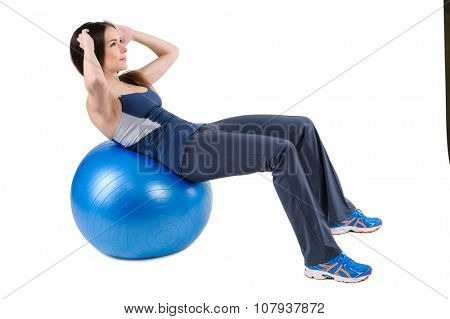 Young woman shows finishing position of Abdominal Fitball Workout, isolated on white
