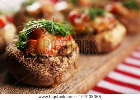 A wooden tablet with stuffed mushrooms and vegetables on the table, close-up
