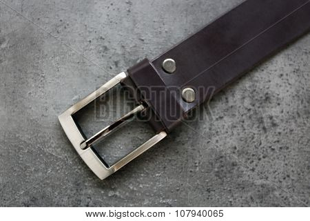 Leather belt with buckle on gray background