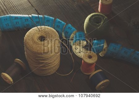 Thread, Needles And  Measuring Meter On Wooden Table